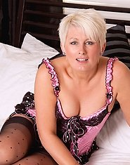Beautiful cougar Sally Taylor masturbates with a massive sex toy in her bedroom